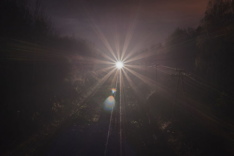 Silhouette trees by illuminated railroad tracks against sky during sunset
