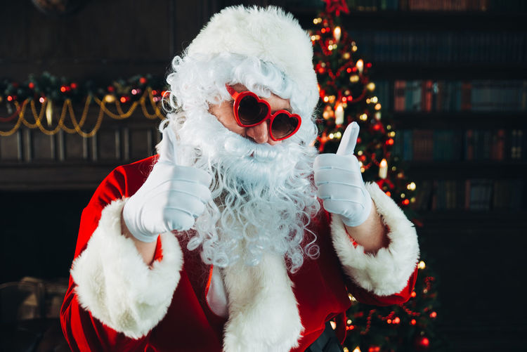 Portrait of man wearing santa claus costume while gesturing thumbs up at home
