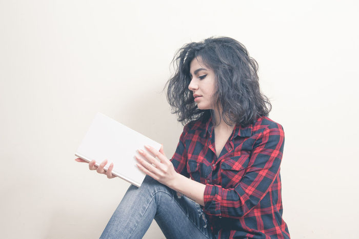 Young woman student with withe book on white background Book Brunette Casual Clothing Copy Space Female Front View Holding Lifestyles Person Portrait Pretty Reading Studio Shot Studying White Background White Covered Bridge Woman Young Adult Young Women