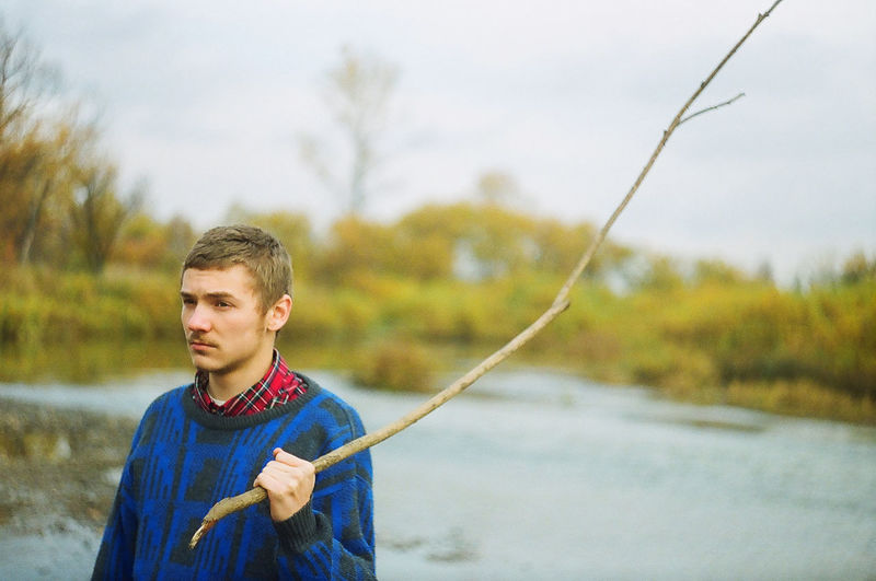 Man holding stick while standing on riverbank against sky