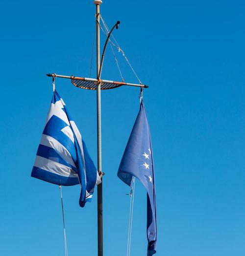 Greece flag and europe flag against a blue sky