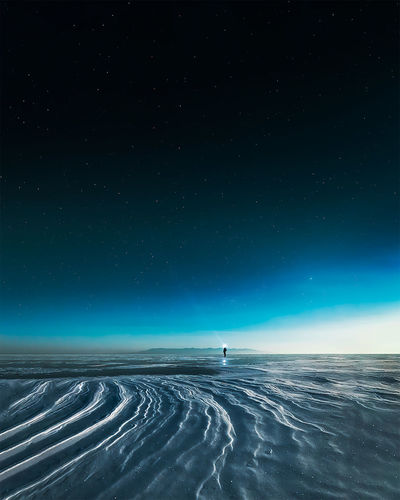 A man in scenic view of snowy landscape against sky at night