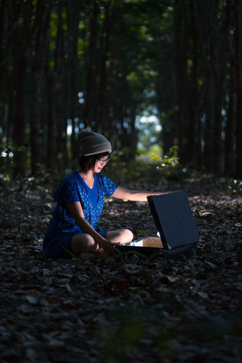 Woman with illuminated suitcase sitting at forest