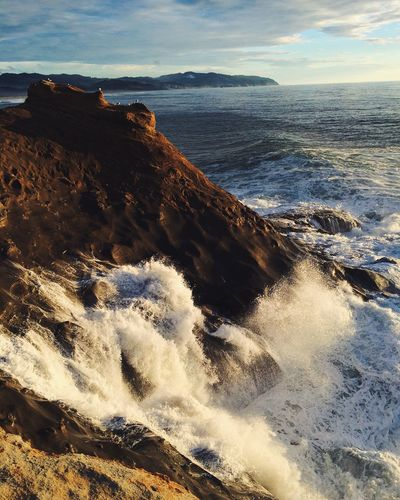 High Angle View Of Waves Splashing On Rocky Shore