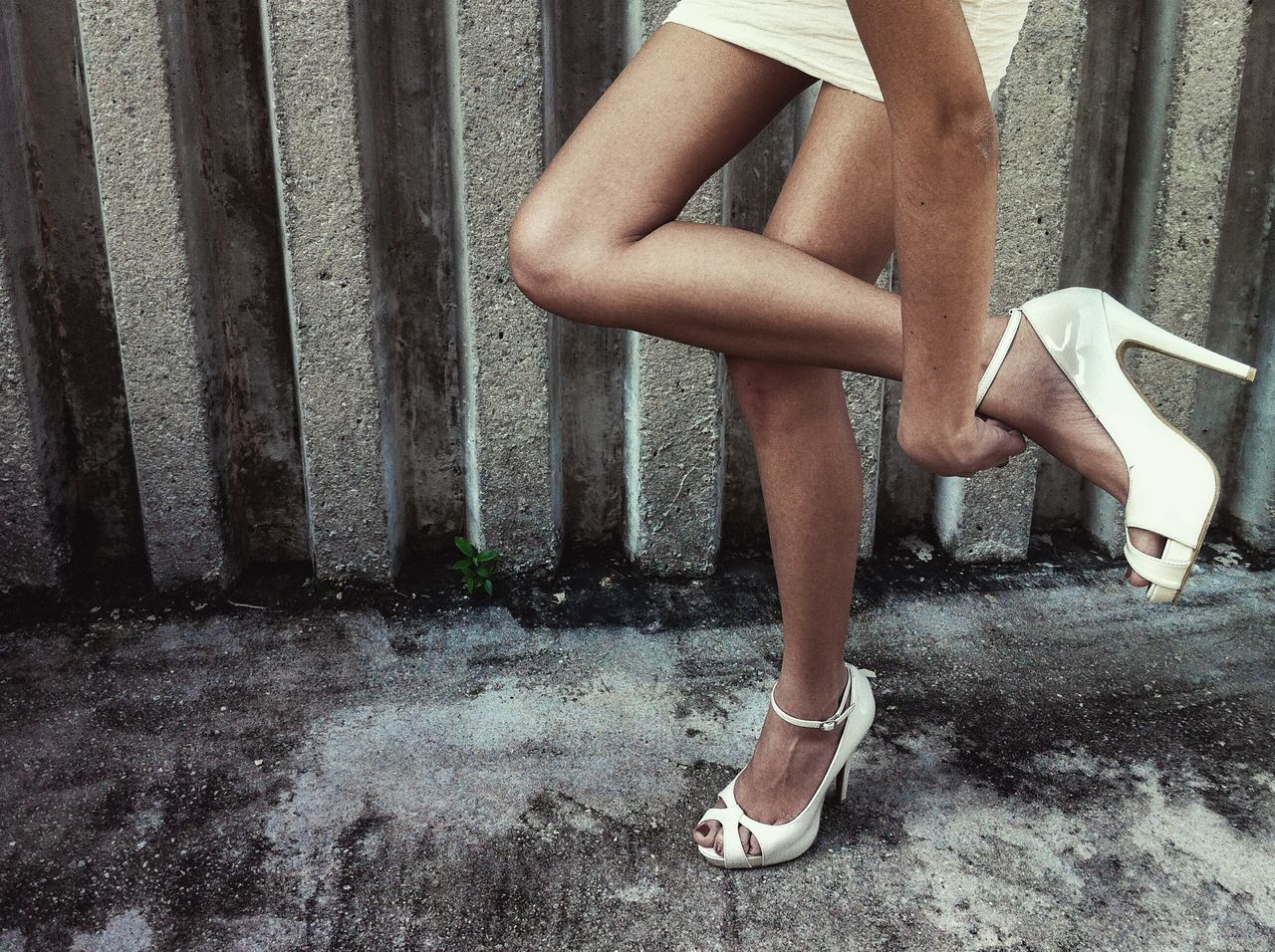 Low Section Of Woman Wearing High Heels On Footpath