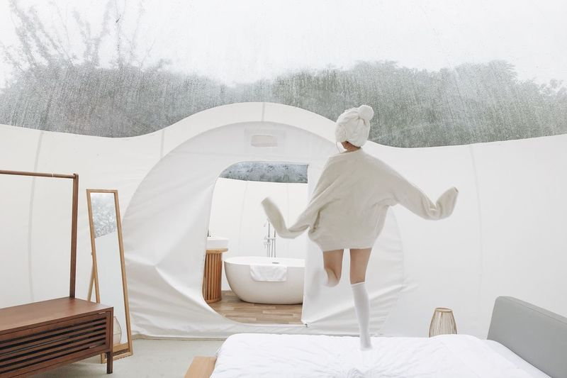 Rear View Of Woman Jumping On Bed In Tent