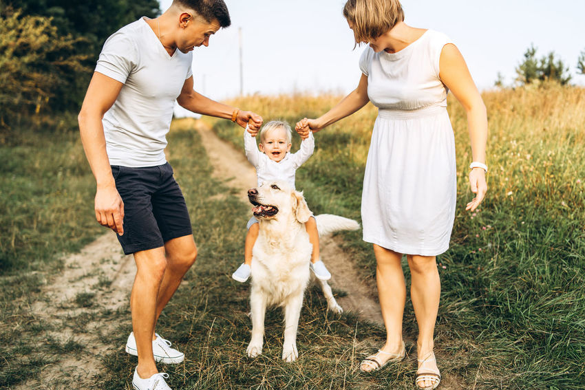 Happy family have fun outdoor Grass Togetherness Men Boy Childhood Family Son Family Love  Family Values Outdoors Having Fun Day Domestic Animals Labrador Father Mother Nature Smiling Happiness Playing Park