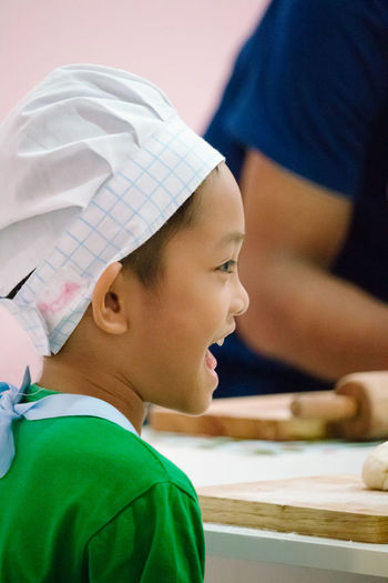 Close-Up Of Happy Child Wearing Chef Hat In Kitchen