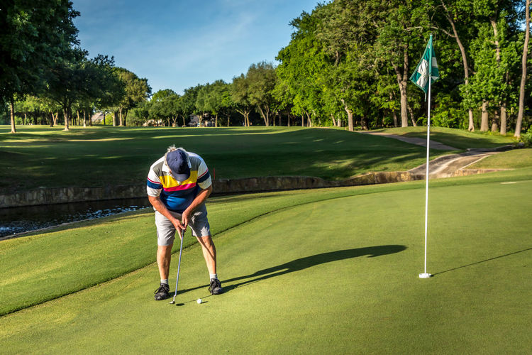 Senior adult man putting the ball on the green, playing golf