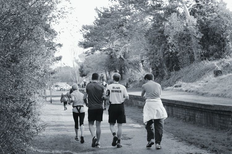 Rear View Of People Jogging On Road