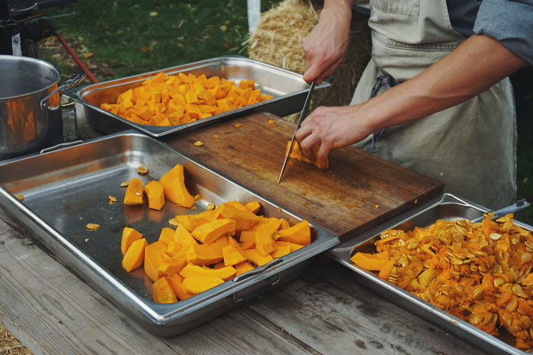 Midsection of chef cutting pumpkin on table