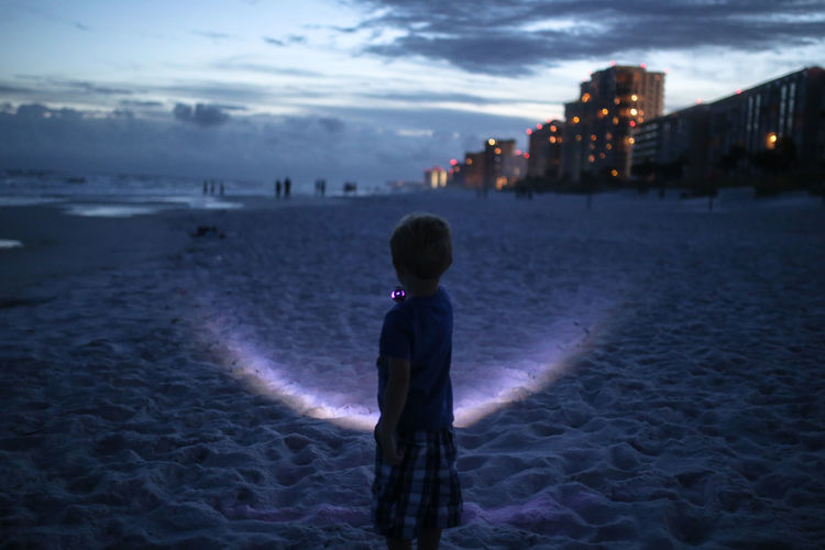 Child standing on beach with flashlight during blue hour Sky Water Child One Person Childhood Land Sea Outdoors Cloud - Sky Blue Hour Bluehour Botany Beach Sandy Beach Night Night Sky Flashlight Summer Nights Sand Ocean
