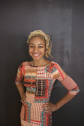 Portrait of smiling young woman standing against black background