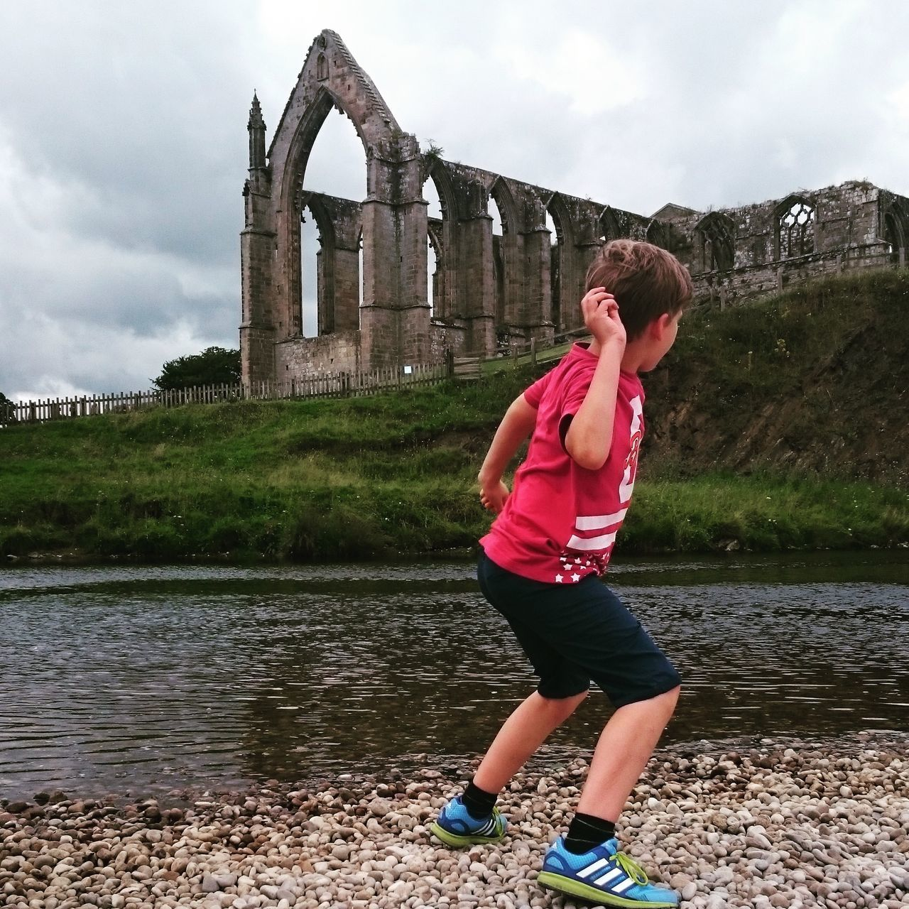 Rear View Full Length Of Boy Throwing Stone In River Against Bolton Abbey