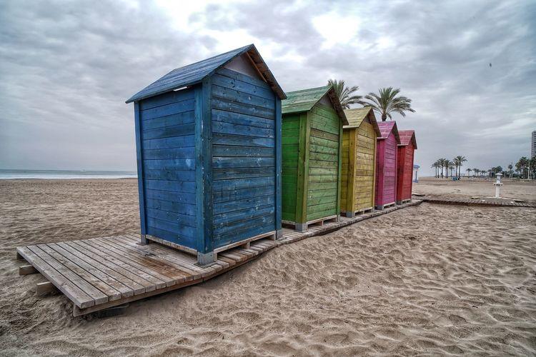 Hut on beach against sky