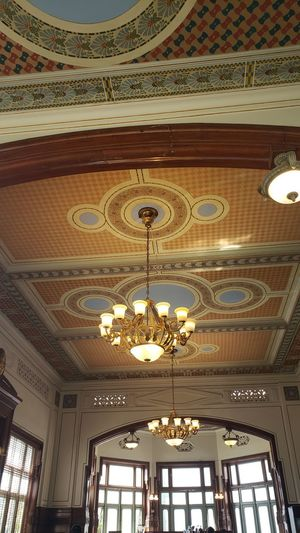 Low angle view of illuminated chandelier hanging in building