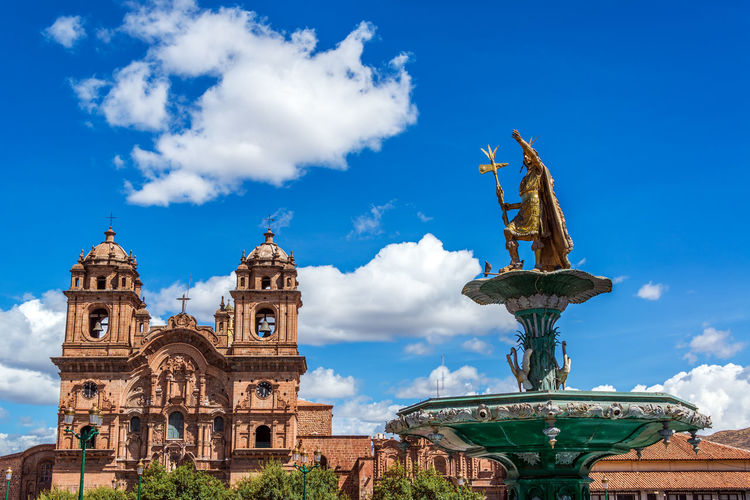 Pachacuti statue and church of the society of jesus against blue sky at plaza de armas