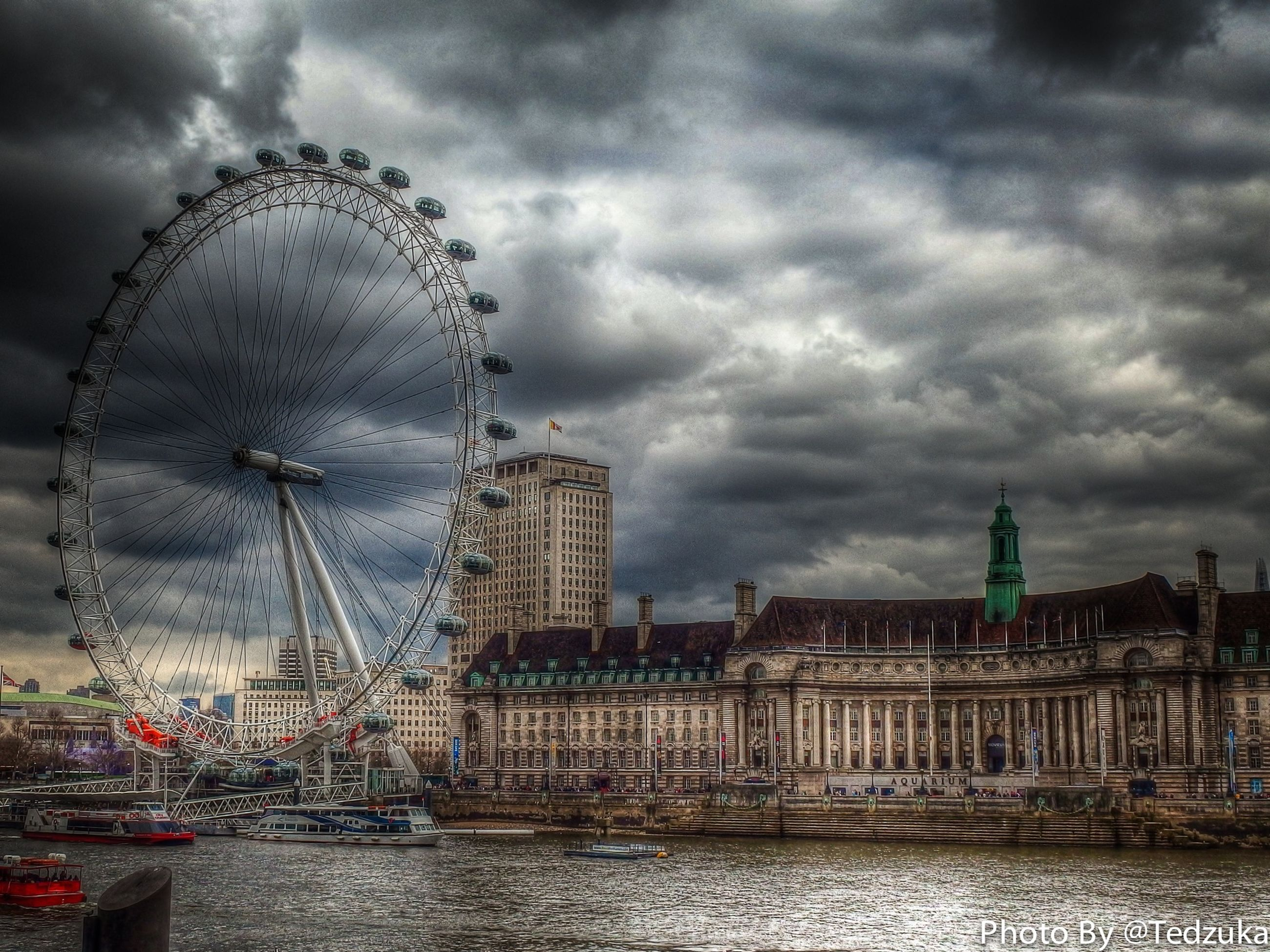 sky, architecture, cloud - sky, cloudy, built structure, building exterior, water, city, weather, ferris wheel, overcast, river, travel destinations, waterfront, capital cities, storm cloud, tall - high, cloud, amusement park ride, famous place