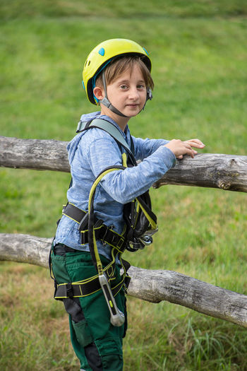 Boy with safety harness and helmet smiling at the camera Boys Casual Clothing Child Childhood Climbing Gear Day Harness Helmet Innocence Leisure Activity Looking At Camera Males  Men Nature One Person Outdoors Plant Portrait Real People Smiling Tree Wood - Material