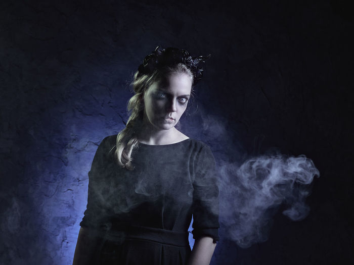 Portrait of spooky woman standing against black background
