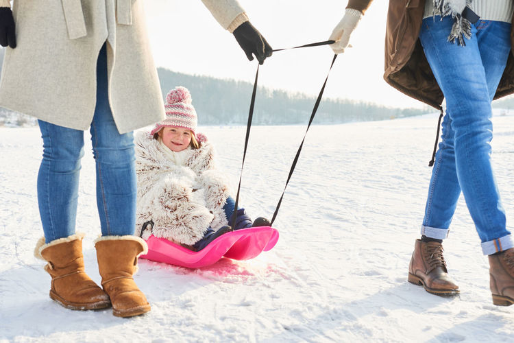 Low section of parents carrying daughter on sled at field