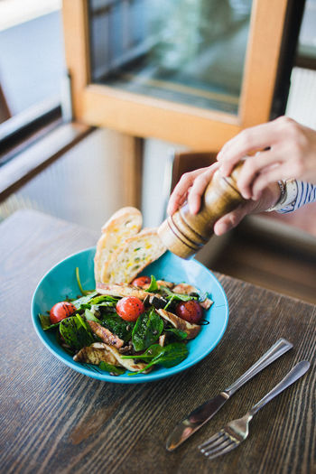 Cropped hand of person holding pepper mill over food in plate on table