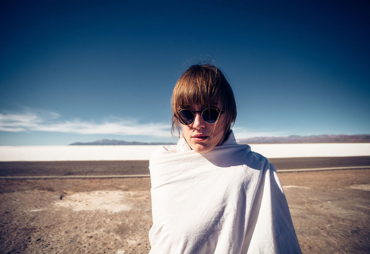 Portrait of woman wearing sunglasses wrapped in blanket standing on land against sky during sunny day