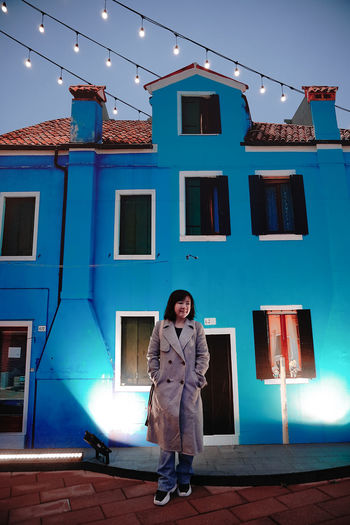 Portrait of woman standing by building against sky