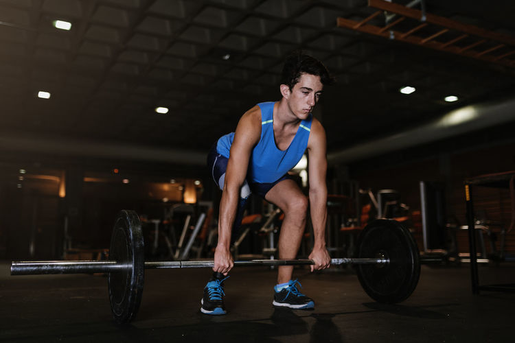 Man with artificial leg lifting dumbbell in gym
