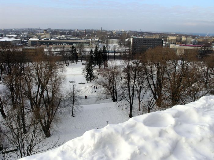 Scenic view of river by city against sky during winter