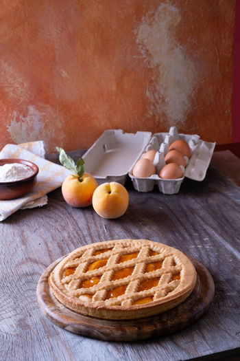 Tart with peach jam on wooden rustic table Apricot Baked Baked Pastry Item Breakfast Dessert Eggs Food Food And Drink Freshness Fruit Healthy Eating Household Equipment Indoors  Indulgence Kitchen Utensil No People Peaches Pie Sweet Sweet Food Table Table Knife Wellbeing Wood - Material