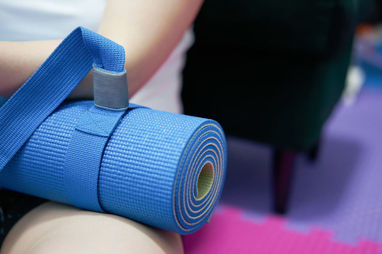 Close-up of person holding yoga mat