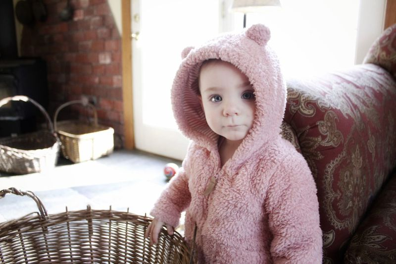 Portrait of cute baby girl in warm clothing standing at home