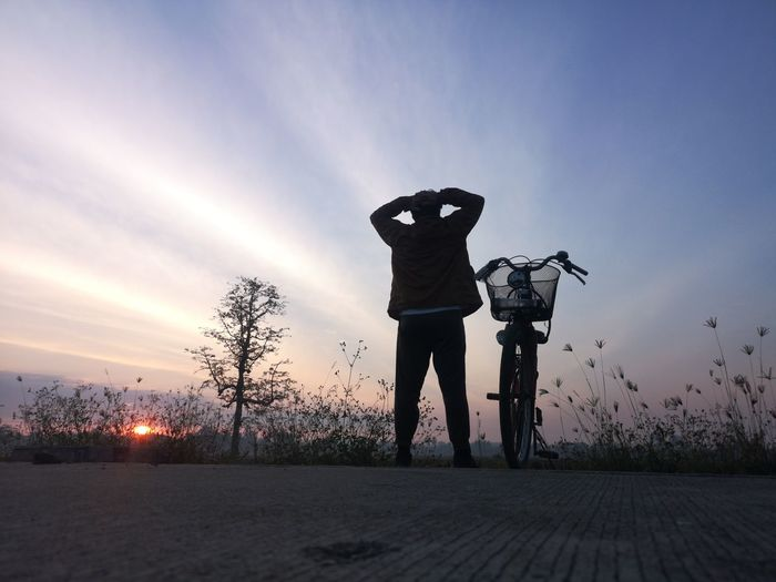 Low angle view of silhouette man photographing on street against sky