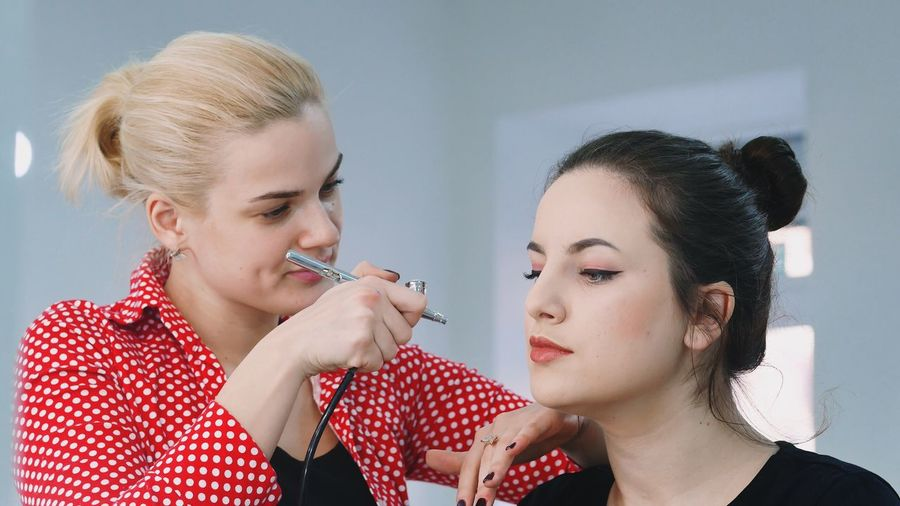 Woman Applying Make-Up With Airbrush To Customer At Studio