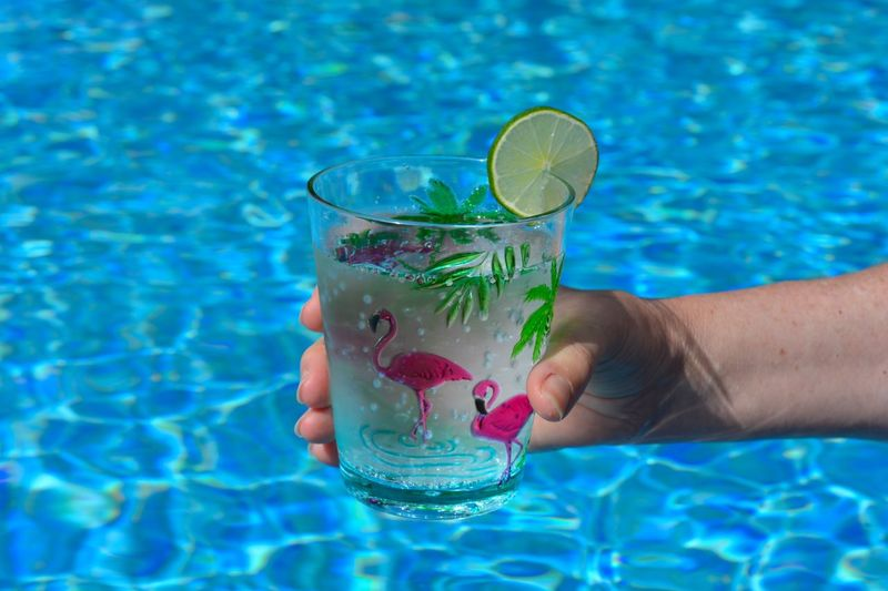 Midsection of person holding drink in swimming pool