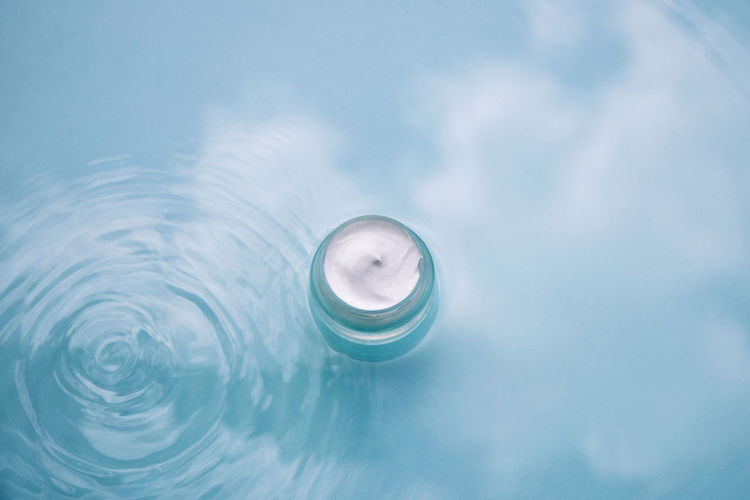 Cosmetic product on water with splashes. jar cream on aqua background, advertising natural cosmetics