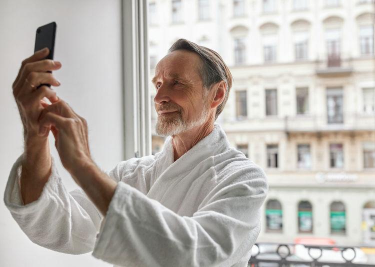 Senior man in bathrobe doing selfie by window at home