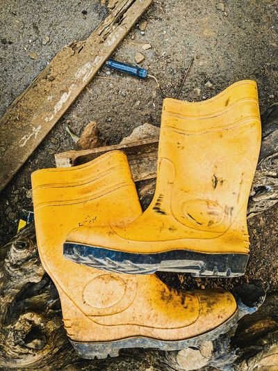 High angle view of old yellow shoes on wood