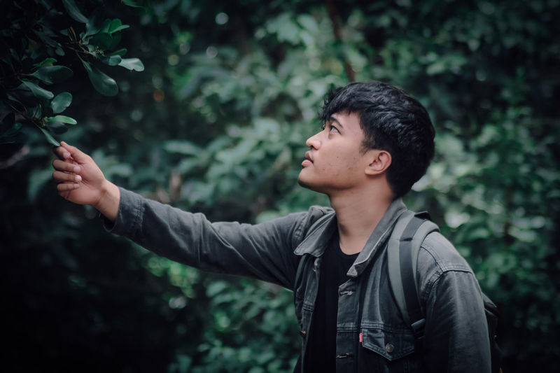 Young man looking away while standing against plants