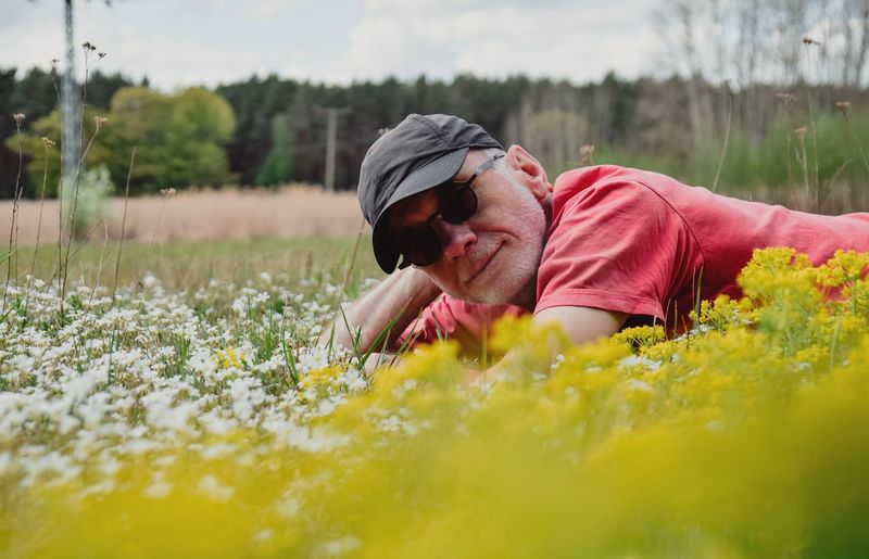 Portrait of man wearing sunglasses while lying on flowers
