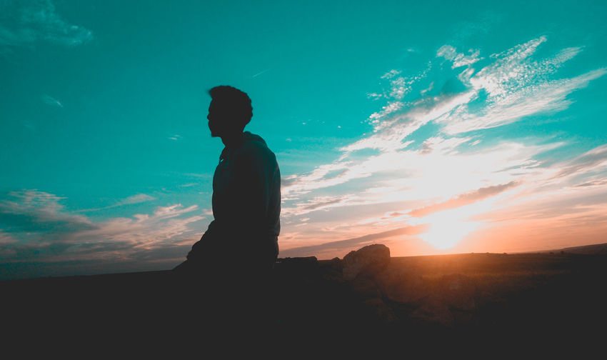 Silhouette Man Sitting Against Sky During Sunset