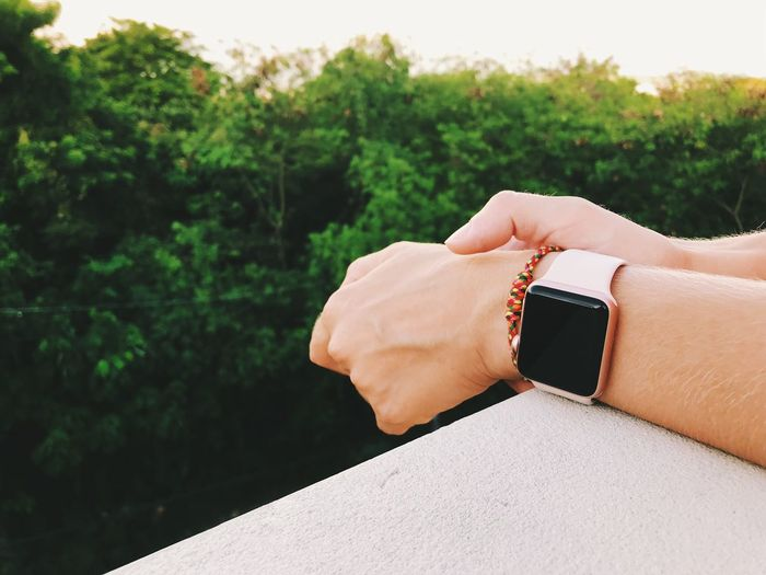 Cropped hands of man wearing smart watch on railing against trees during sunset