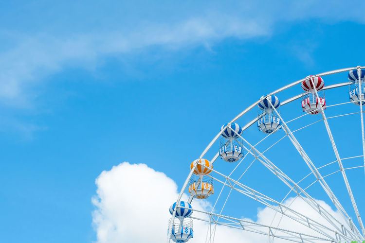 Amusement Park Ride Sky Amusement Park Cloud - Sky Low Angle View Ferris Wheel Nature Blue Arts Culture And Entertainment Day No People Outdoors Leisure Activity Ride Fairground Fun Travel Shape Emotion Enjoyment Yellow Red White Clouds