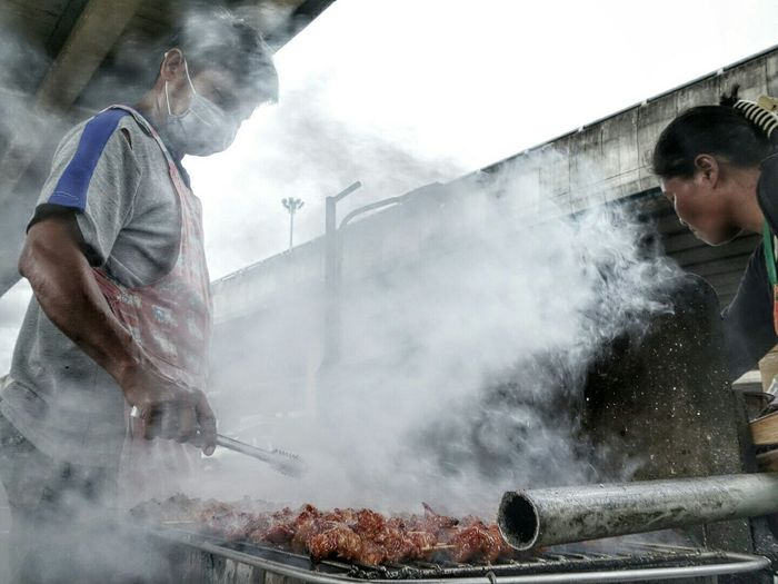 Two people cooking food in street