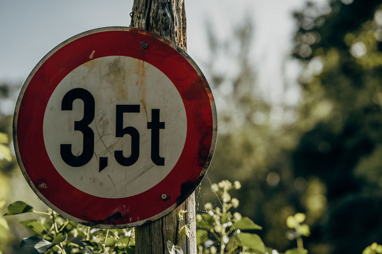 Close-up of road sign on wooden post