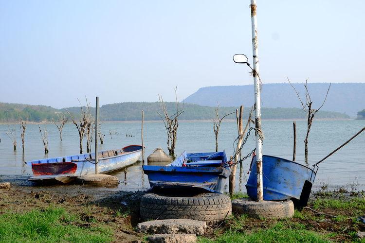 Boats moored on beach against clear sky