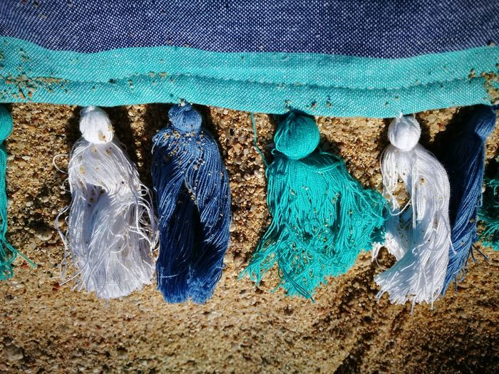 High angle view of fabric with tassels on sand