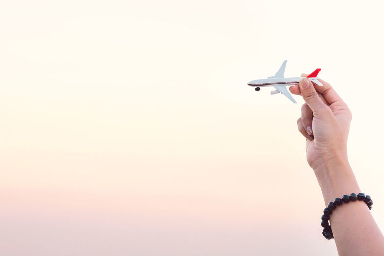 Woman hand holding airplane model in sunset sky and summer sea background dreams of journey in vacation. Travel and air transportation concept. Taking flight and takeoff, Hand with small toy plane. Hands Transportation Travel Vacations Air Vehicle Airplane Body Part Close-up Copy Space Destination Finger Flight Hand Holding Human Body Part Human Hand Indoors  Leisure Activity Lifestyles Nature Personal Perspective Sky Sunset Toy Travel Destinations