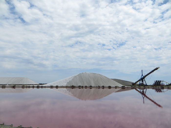 Mountains of salt and pools of purple salt in reflection Cloud - Sky Sky Water Day Nature No People Beauty In Nature Mineral Reflection Waterfront Scenics - Nature Tranquil Scene Tranquility Outdoors Mountain Salt - Mineral Environment Sea Salt Flat Pools  Mountain Salt